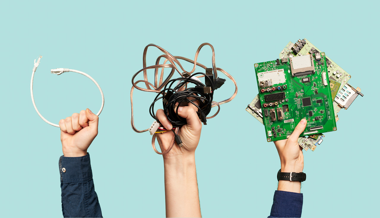 Three hands hold electrical waste on blank blue background. Ecological clean garbage concept.
